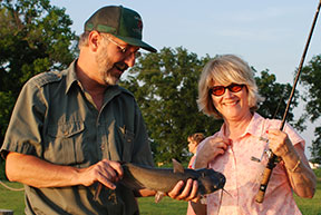 Oklahoma Department of Wildlife Conservation employee holding a channel catfish for a female participant at a fishing clinic